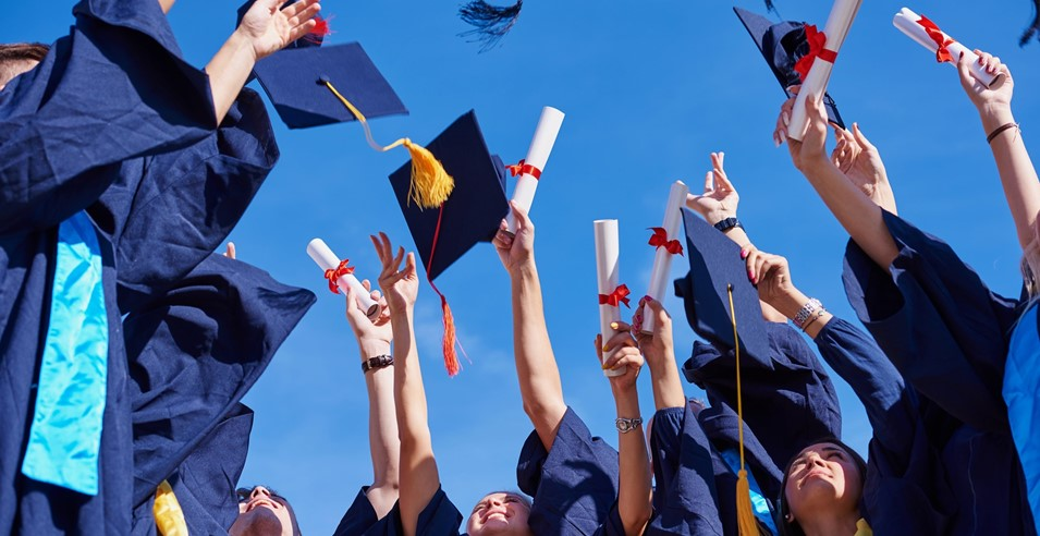 Graduates throwing caps in air while holding diplomas
